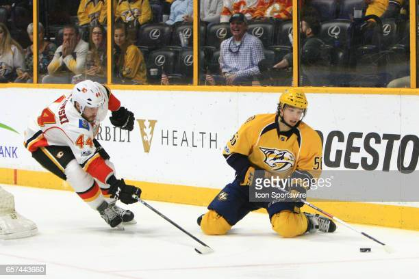 Nashville Predators left wing Kevin Fiala tries to play the puck from the ice as Calgary Flames defenseman Matt Bartkowski extends his stick during...