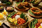 Nasi Campur Bali, a popular traditional Balinese rice dish of steamed rice served with variety side dishes. Some of the side dishes are served together with the rice on the plate; while there are seve
