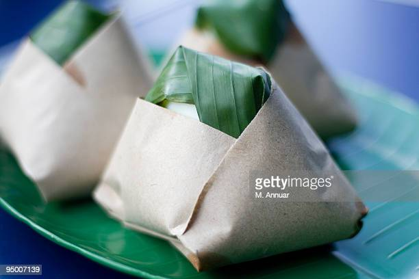 Nasi lemak wrapped in paper and banana leaf