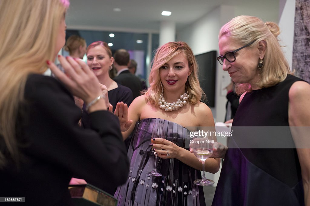 Nasiba Adilova and Cindy Rachofsky discus the new jewelry of Sabine Ghanem during the Young Collectors Two x Two Cocktail party at the Rachofsky House on October 25, 2013 in Dallas, Texas.