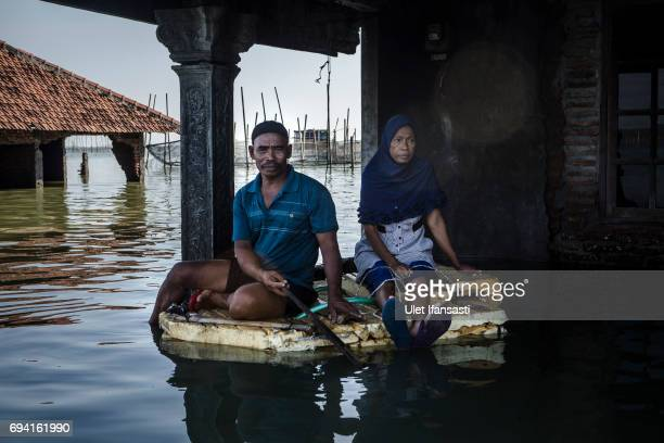 Nasikin and his wife Warsipah pose infront of their house which has been eighteen years living in a house surrounded by rising sea levels at Sriwulan...