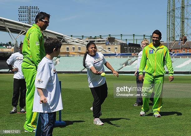 Nasir Jamshed and Asad Shafiq of Pakistan watch over and play a game of cricket with young fans from Curwen Primary School as members of the Pakistan...