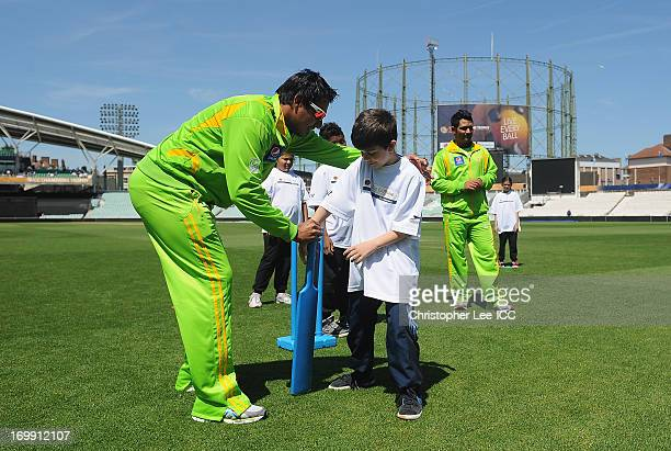 Nasir Jamshed of Pakistan gives some tips to a young player as they play a game of cricket with young fans from Curwen Primary School as members of...