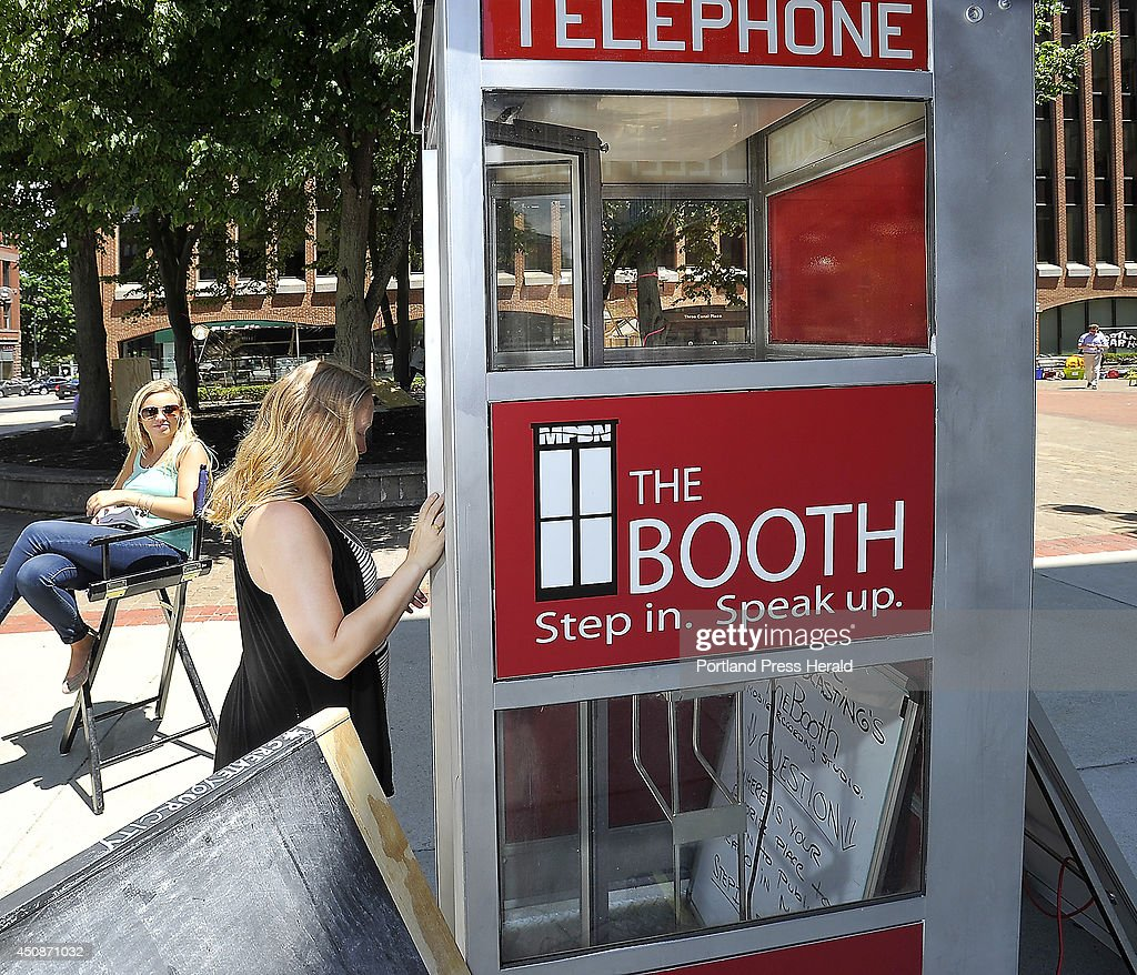 Natalie Brenner, an intern at MPBN from North Carolina, works the telephone booth encouraging passersby, in this case Sasha Salzberg of Portland, to step in and give a suggestion on how to make Portland better.