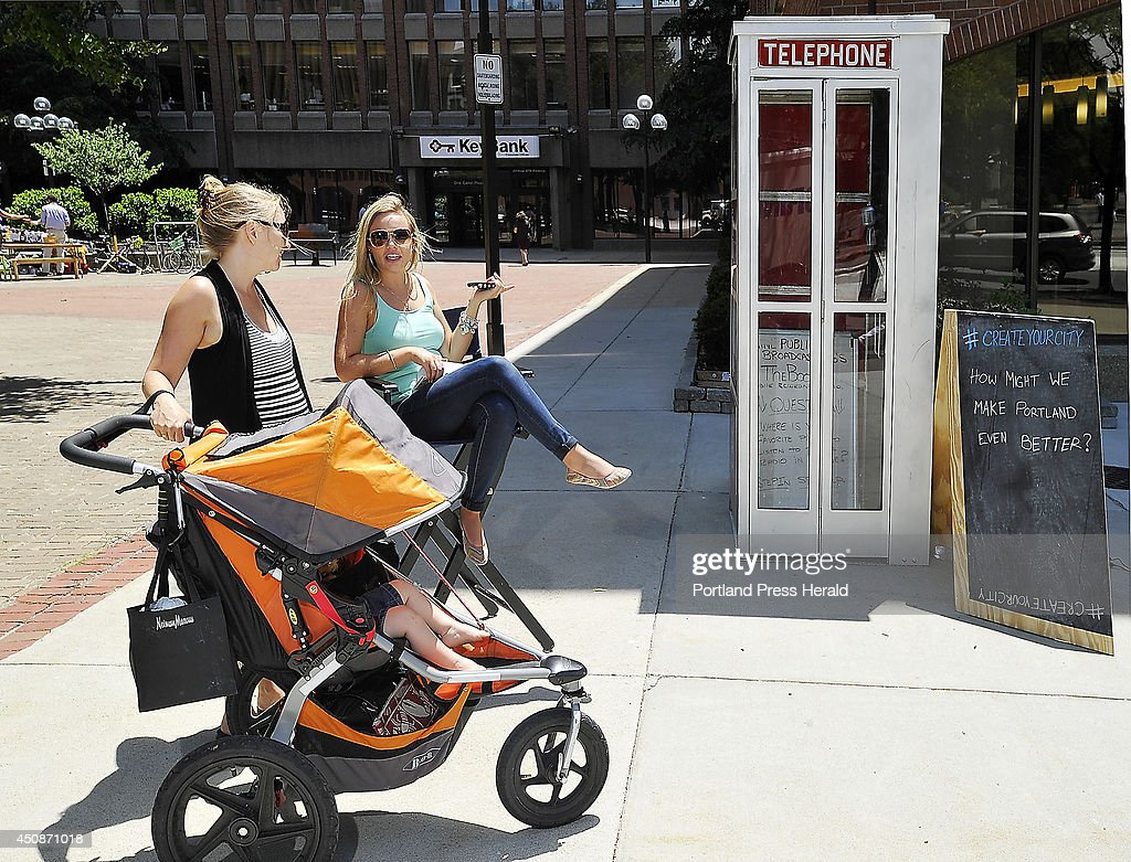 Natalie Brenner, second from left, an intern at MPBN from North Carolina, works the telephone booth encouraging passersby to step in and give a suggestion on how to make Portland better.