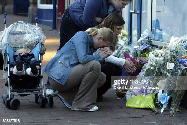 Natalie Brown kneels in front of flowers left at the Greggs bakery in Carlisle where a 10 month old baby was stabbed to death