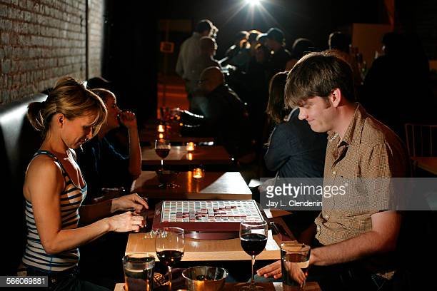 Natalie Chaidez left from Pasadena and Scott Lowe from Glendale get in a game of Scrabble while drinking some wine at the Echo Park bar '1642' May 12...