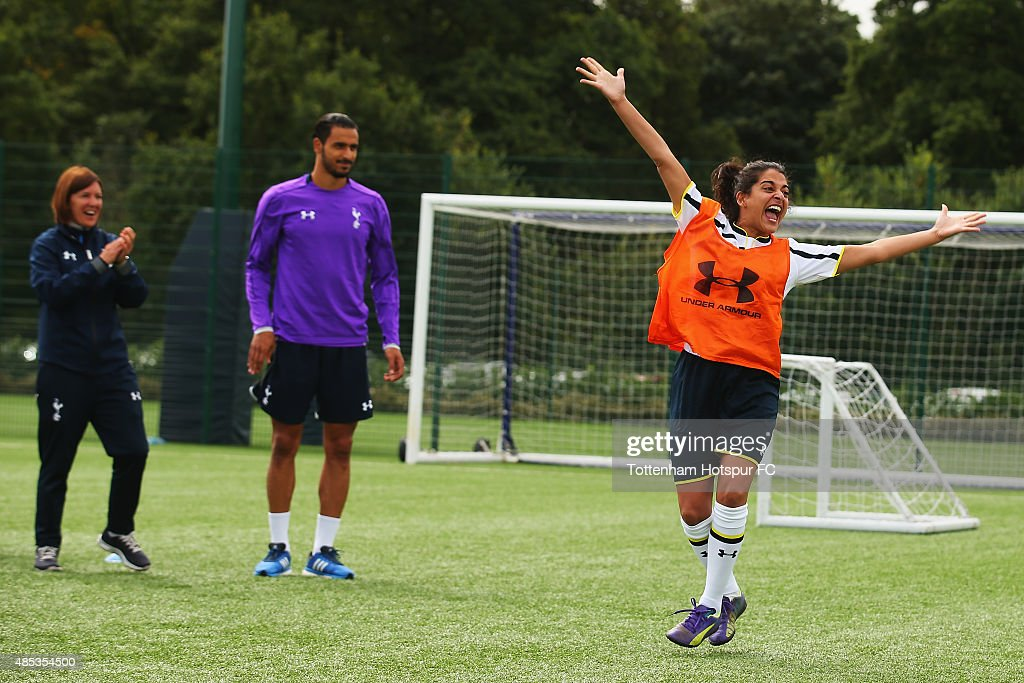 Natalie Dew of Bent it Like Beckham celebrates after taking a free kick as Nacer Chadli of Spurs and Spurs Ladies Head Coach Karen Hills look on during a training session where Tottenham Hotspur Ladies Coach the Cast of 'Bend it Like Beckham' on August 27, 2015 in Enfield, England.