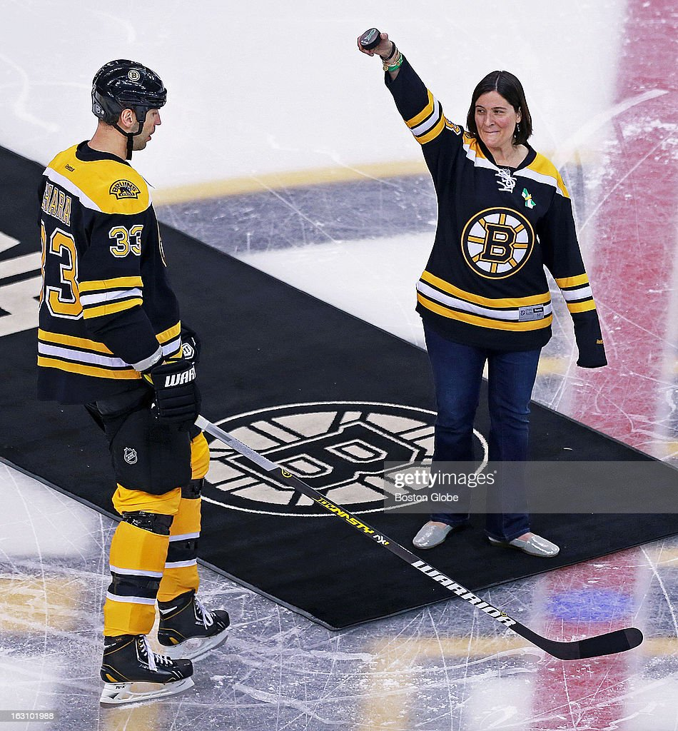 Natalie Hammond, a teacher at the Sandy Hook Elementary School in Newtown, Conn., acknowledges the cheers of the crowd before she dropped a ceremonial first puck before the game, as Bruins captain Zdeno Chara looks on at left. The Boston Bruins hosted the Montreal Canadiens in a regular season NHL hockey game at the TD Garden.