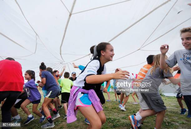 Natalie Ryan of Scarborough runs under a parachute during a game at Fish Camp in South Portland The husband and wife team of Jeff and Deb Sandler...