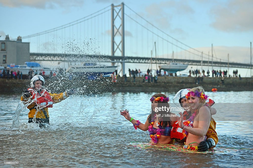 Natalie Tuccia and Sarah Johnston put their arms around a RNLI member as they join around 1,000 New Year swimmers, many in costume, in front of the Forth Rail Bridge during the annual Loony Dook Swim in the River Forth on January 1, 2013 in South Queensferry, Scotland. Thousands of people gathered last night to see in the New Year at Hogmanay celebrations in towns and cities across Scotland.