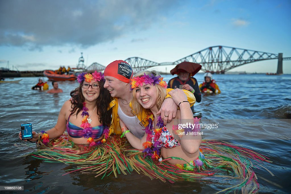 Natalie Tuccia and Sarah Johnston put their arms around another swimmer as they joined around 1,000 New Year swimmers, many in costume, braved freezing conditions in the River Forth in front of the Forth Rail Bridge during the annual Loony Dook Swim on January 1, 2013 in South Queensferry, Scotland. Thousands of people gathered last night to see in the New Year at Hogmanay celebrations in towns and cities across Scotland..
