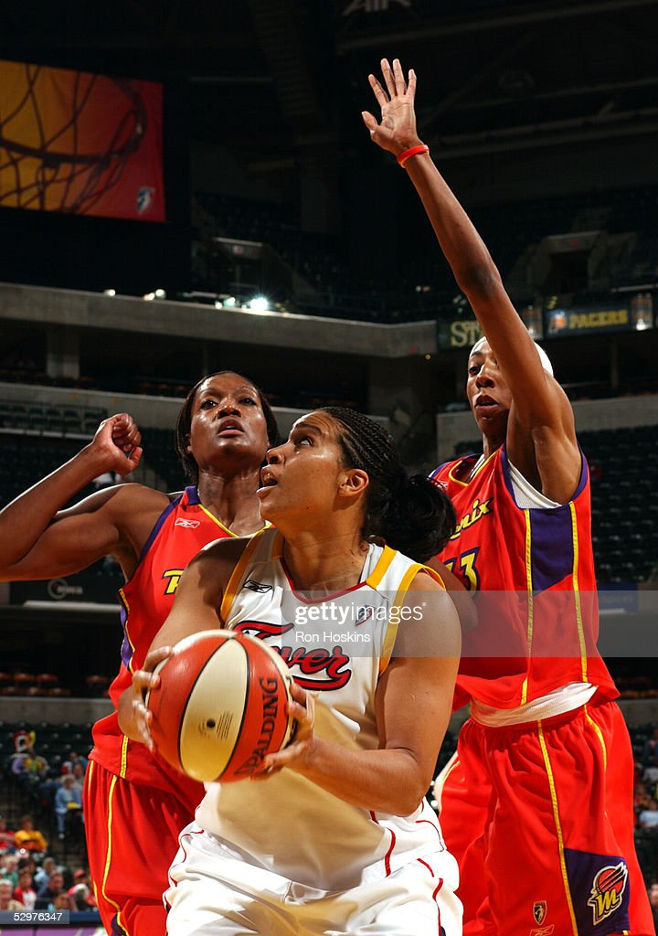Natalie Williams of the Indiana Fever looks to score over Ashley Robinson and Angelina Williams of the Phoenix Mercury on May 24 2005 at Conseco...