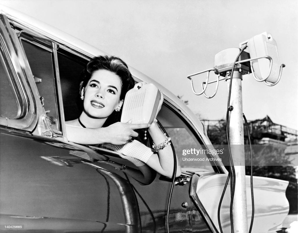 Natalie Wood displays the new drive in-movie speakers as she leans out of her car window, Hollywood, California, 1957.