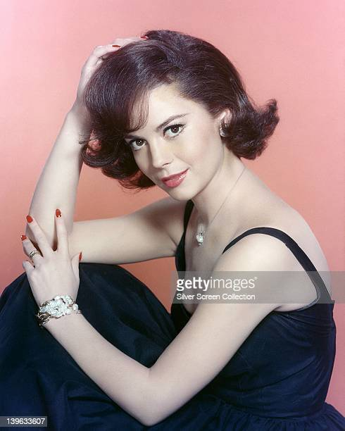 Natalie Wood US actress wearing a dark blue dress in a studio portrait against a pink background circa 1965