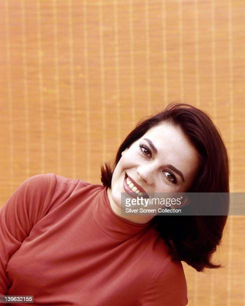 Natalie Wood US actress wearing a red top smiling in a studio portrait against a yellow background circa 1965