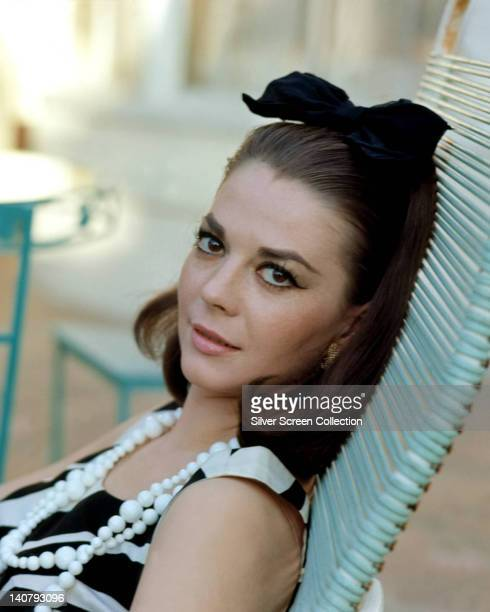 Natalie Wood US actress wearing a white beaded necklace and a sleeveless black and white dress reclining with a black bow in her hair circa 1965