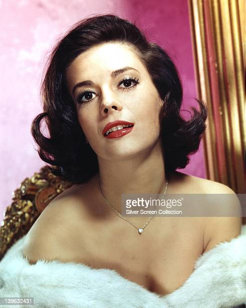 Natalie Wood US actress wrapped in a white fur stole exposing her shoulders with a silver chain around her neck in a studio portrait circa 1970