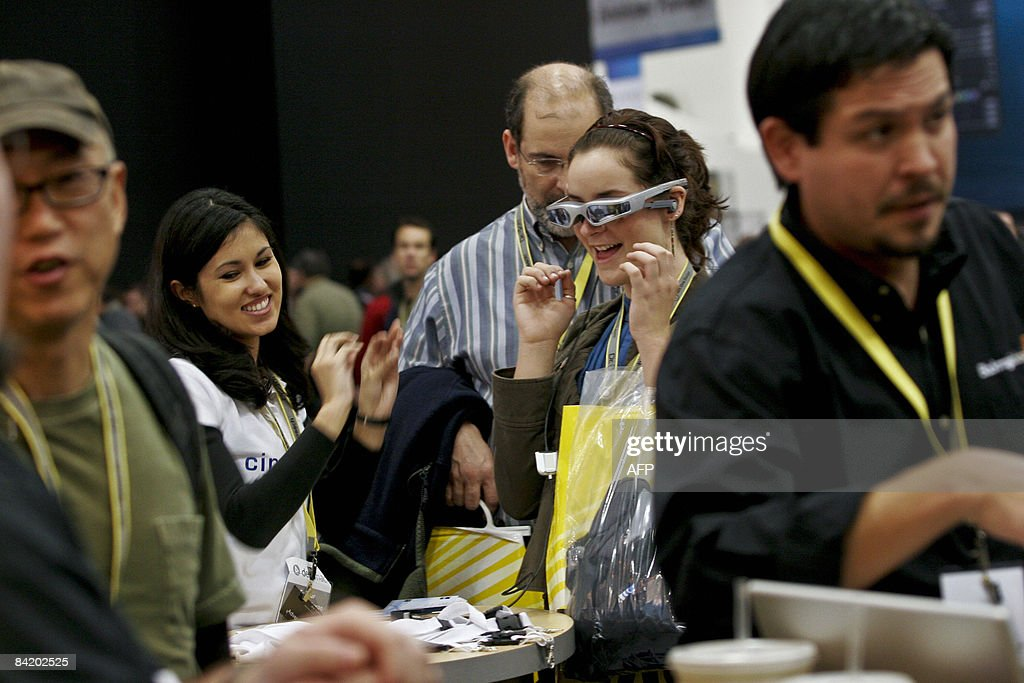 Natasha Asbury (2nd-L) demonstrates for Breanna Sooter (2nd-R) and her father Eric (3rd-R) how movies can be watched using the Cinemizer video eyewear during the Macworld Expo 2009 in San Francisco, CA, Wednesday, January 7, 2009. Tens of thousands of Macintosh consumers as well as Apple engineers and developers attended the annual technology fair where new Mac-compatible products were showcased along with the release of Apple's latest computer gadgets and software updates. AFP PHOTO / Ryan ANSON