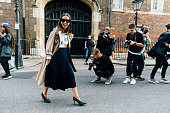 Natasha Goldenberg wears a tan trench coat with a belted skirt and green heels during London Fashion Week Spring Summer 2016 on September 19 2015 in...