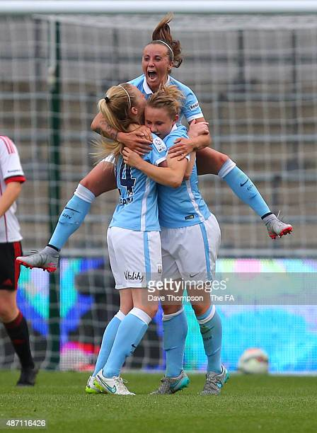 Natasha Harding jumps on the back of Isobel Christiansen of Manchester City after Christiansen scored the first goal of the game during the Women's...