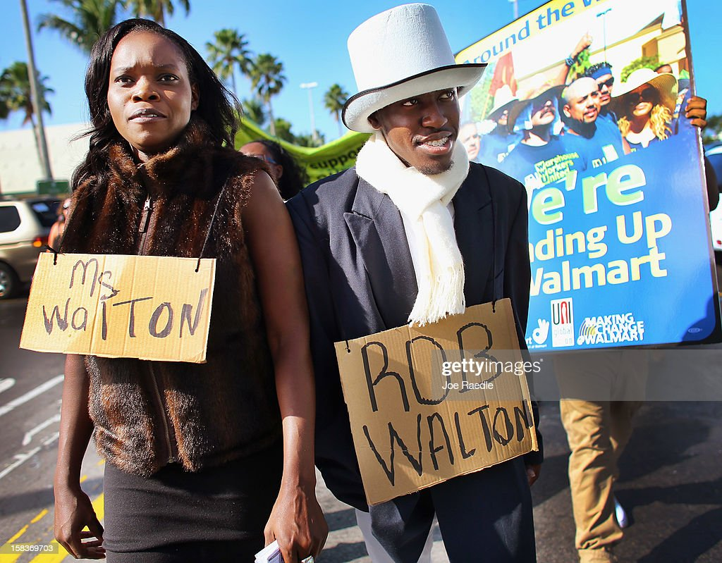 Natasha Royal (L) and Wesley Miller participate in a 'Global Day' of action against Walmart on December 14, 2012 in Hialeah, Florida. The protesters in partnership with the global union federation UNI, the union-affiliated group Making Change at Walmart joined others around the world to among other things call for an end to alleged retaliation against US Walmart worker activists.