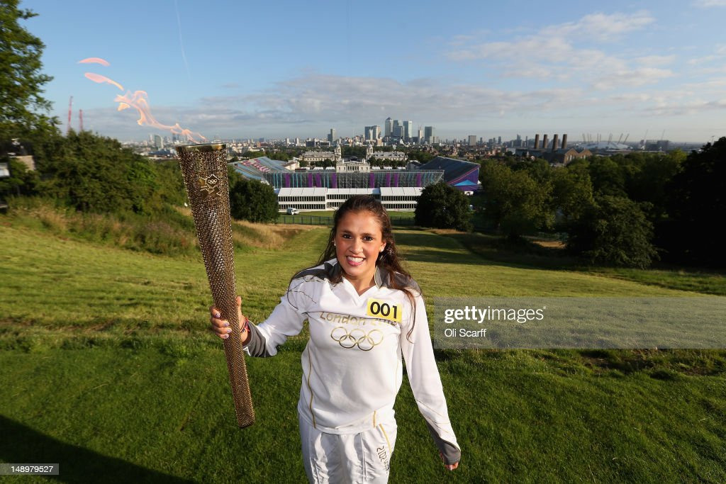 Natasha Sinha, 15, holds the Olympic torch aloft in front of a view of central London at the Observatory in Greenwich Park on July 21, 2012 in London, England. The 64th day of the Olympic torch relay will see torchbearers carry the flame through the capital for the first full day in London ahead of the 2012 Olympic Games.