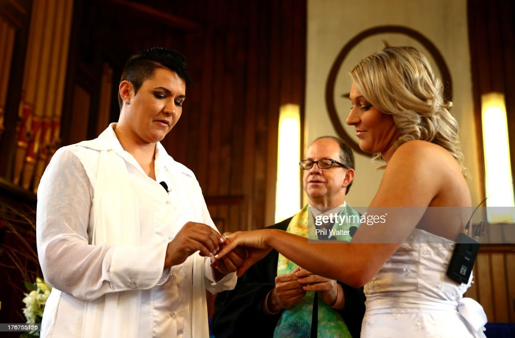 Natasha Vitali (L) and Melissa Ray (R) exchange rings with marriage celebrant Rev Matt Tittle at the Auckland Unitary Church on August 19, 2013 in Auckland, New Zealand. New Zealand passed a bill to legalizen same-sex marriage as of August 19, 2013. New Zealand is the first coutry in Oceania to leaglize same-sex marriage.