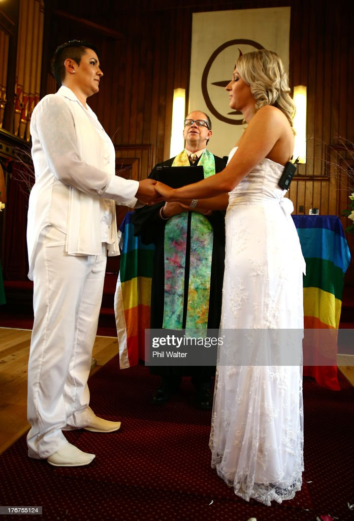Natasha Vitali (L) and Melissa Ray (R) exchange vows with marriage celebrant Rev Matt Tittle at the Auckland Unitary Church on August 19, 2013 in Auckland, New Zealand. New Zealand passed a bill to legalizen same-sex marriage as of August 19, 2013. New Zealand is the first coutry in Oceania to leaglize same-sex marriage.