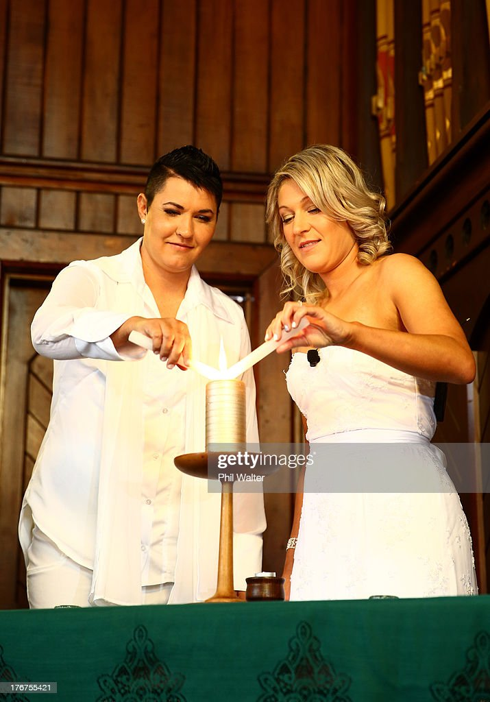 Natasha Vitali (L) and Melissa Ray (R) light a candle during their wedding at the Auckland Unitary Church on August 19, 2013 in Auckland, New Zealand. New Zealand passed a bill to legalizen same-sex marriage as of August 19, 2013. New Zealand is the first coutry in Oceania to leaglize same-sex marriage.