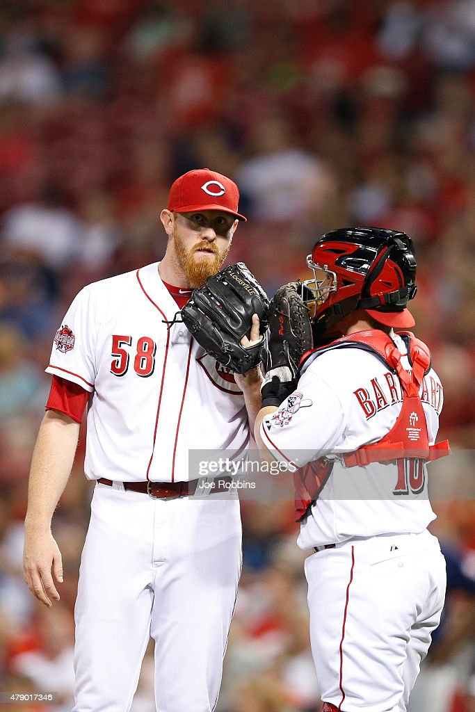 Nate Adcock #58 and Tucker Barnhart #16 of the Cincinnati Reds talk in the sixth inning against the Minnesota Twins at Great American Ball Park on June 29, 2015 in Cincinnati, Ohio.