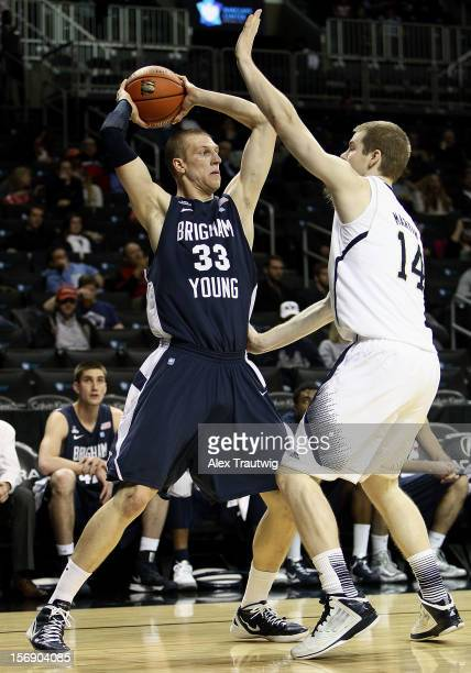 Nate Austin of the Brigham Young Cougars looks to pass as Scott Martin of the Notre Dame Fighting Irish defends during the consolation game of the...