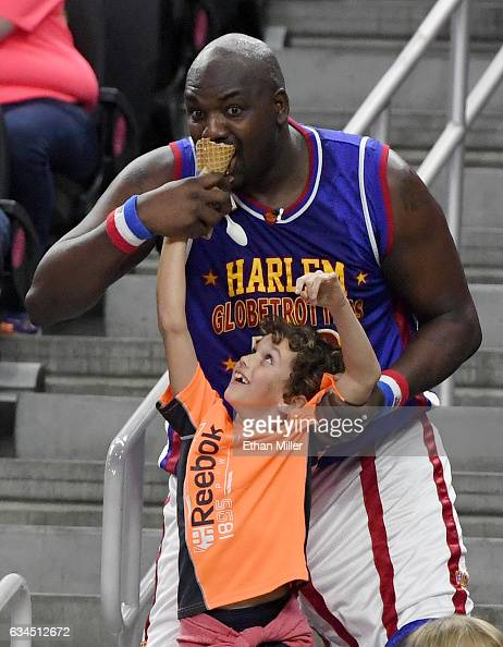 Nate 'Big Easy' Lofton of the Harlem Globetrotters takes a bite of 8yearold Jacob Ross's ice cream cone during the team's exhibition game against the...