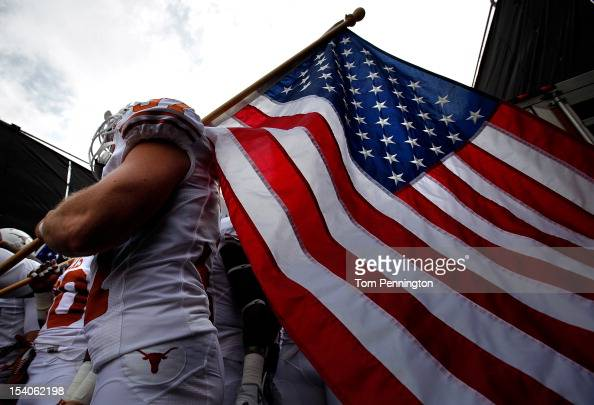 Nate Boyer of the Texas Longhorns carries an American flag as the Texas Longhorns take to the field against the Oklahoma Sooners at Cotton Bowl on...