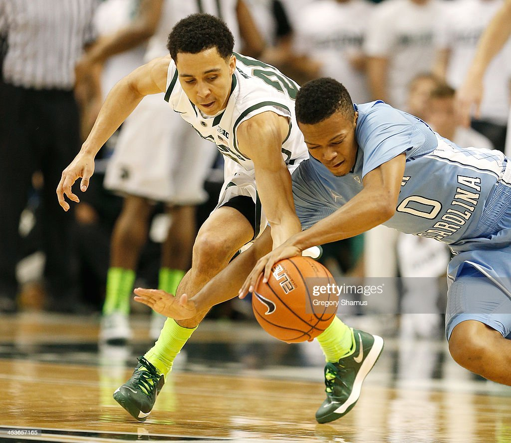 Nate Britt #0 of the North Carolina Tar Heels battles for the ball with Branden Dawson #22 of the Michigan State Spartans during the second half at the Jack T. Breslin Student Events Center on December 4, 2013 in East Lansing, Michigan. North Carolina won the game 79-65.