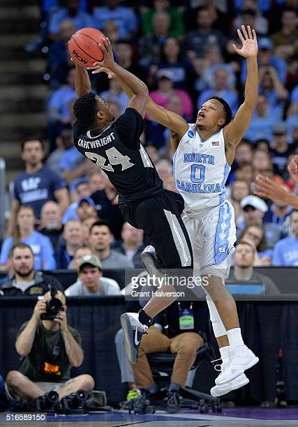 Nate Britt of the North Carolina Tar Heels defends a shot by Kyron Cartwright of the Providence Friars during the second round of the NCAA Men's...