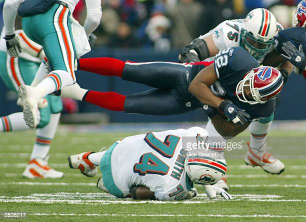 Nate Clements of the Buffalo Bills is knocked off his feet by Wade Smith of the Miami Dolphins on December 21 2003 at Ralph Wilson Stadium in Orchard...
