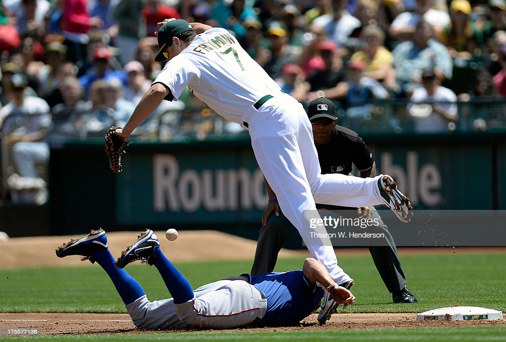 <a gi-track='captionPersonalityLinkClicked' href=/galleries/search?phrase=Nate+Freiman&family=editorial&specificpeople=9750566 ng-click='$event.stopPropagation()'>Nate Freiman</a> #7 of the Oakland Athletics has the ball thrown past him for an error by Josh Donaldson #20 (not pictured) allowing David Murphy #7 of the Texas Rangers to get up and go to second base in the second inning at O.co Coliseum on August 4, 2013 in Oakland, California.