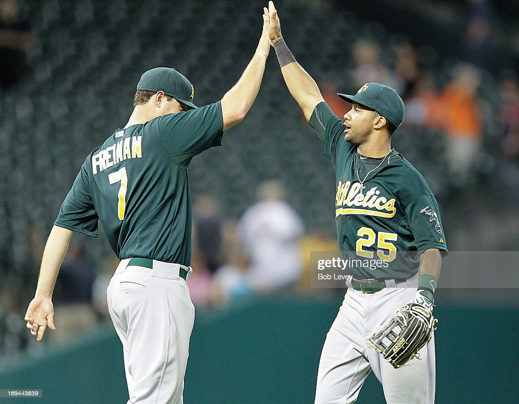Nate Freiman #7 of the Oakland Athletics high fives Chris Young #25 of the Oakland Athletics whose three run home run in the ninth inning gave the Oakland Athletics a 6-5 win over the Houston Astros at Minute Maid Park on May 24, 2013 in Houston, Texas.