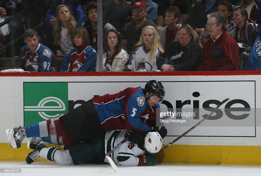 <a gi-track='captionPersonalityLinkClicked' href=/galleries/search?phrase=Nate+Guenin&family=editorial&specificpeople=3948510 ng-click='$event.stopPropagation()'>Nate Guenin</a> #5 of the Colorado Avalanche takes <a gi-track='captionPersonalityLinkClicked' href=/galleries/search?phrase=Charlie+Coyle&family=editorial&specificpeople=7029381 ng-click='$event.stopPropagation()'>Charlie Coyle</a> #3 of the Minnesota Wild to the ice in Game One of the First Round of the 2014 NHL Stanley Cup Playoffs at Pepsi Center on April 17, 2014 in Denver, Colorado. The Avalanche defeated the Wild 5-4 in overtime to take a 1-0 game advantage in the series.