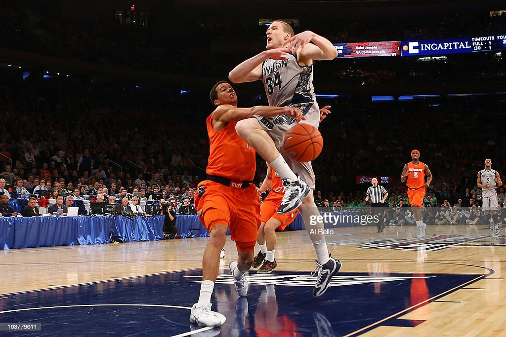 Nate Lubick #34 of the Georgetown Hoyas has the ball knocked loses as he drove to the basket in the second half against Michael Carter-Williams #1 of the Syracuse Orange during the semifinals of the Big East Men's Basketball Tournament at Madison Square Garden on March 15, 2013 in New York City.