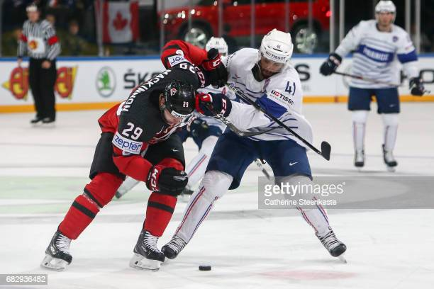 Nate Mackinnon of Canada challenges Pierre Edouard Bellemare of France for the puck during the 2017 IIHF Ice Hockey World Championship game between...