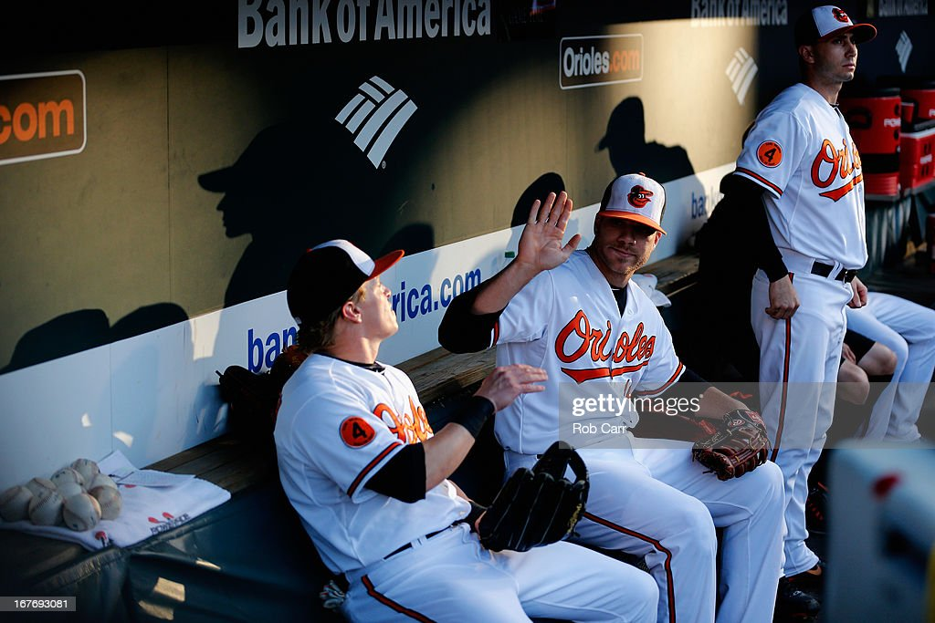 Nate McLouth #9 (L), Chris Davis #19 (C) and starting pitcher Miguel Gonzalez #50 of the Baltimore Orioles sit in the dugout before taking the field against the Toronto Blue Jays at Oriole Park at Camden Yards on April 23, 2013 in Baltimore, Maryland.