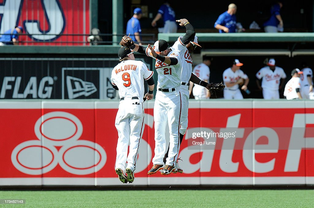 Nate McLouth #9, Nick Markakis #21 and Adam Jones #10 of the Baltimore Orioles celebrate after a 7-4 victory against the Toronto Blue Jays at Oriole Park at Camden Yards on July 14, 2013 in Baltimore, Maryland.