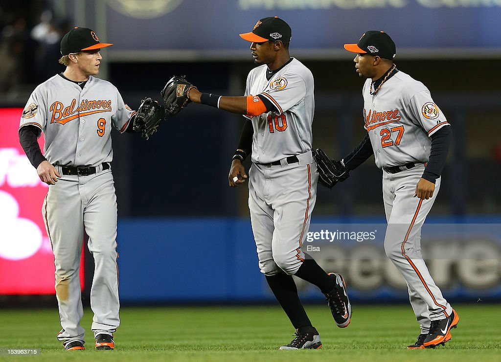 Nate McLouth #9 of the Baltimore Orioles, Adam Jones #10, and Endy Chavez #27 of the Baltimore Orioles celebrate after defeating the New York Yankees in thirteen innings in Game Four of the American League Division Series at Yankee Stadium on October 11, 2012 in the Bronx borough of New York City.