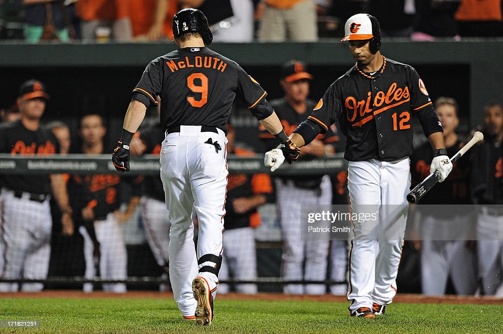Nate McLouth #9 of the Baltimore Orioles celebrates with teammate Alexi Casilla #12 after hitting a solo home run against the New York Yankees in the seventh inning at Oriole Park at Camden Yards on June 28, 2013 in Baltimore, Maryland. The Baltimore Orioles won, 4-3.