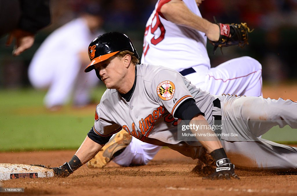 Nate McLouth #9 of the Baltimore Orioles dives back into first base after a pickoff attempt by the Boston Red Sox during the ninth inning on August 29, 2013 at Fenway Park in Boston Massachusetts.