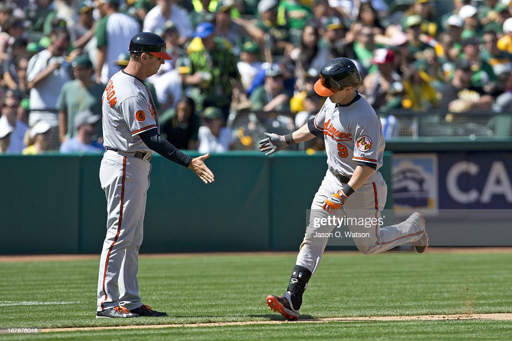 <a gi-track='captionPersonalityLinkClicked' href=/galleries/search?phrase=Nate+McLouth&family=editorial&specificpeople=536572 ng-click='$event.stopPropagation()'>Nate McLouth</a> #9 of the Baltimore Orioles is congratulated by Bobby Dickerson #11 while rounding the bases after hitting a home run against the Oakland Athletics during the eighth inning at O.co Coliseum on April 27, 2013 in Oakland, California.