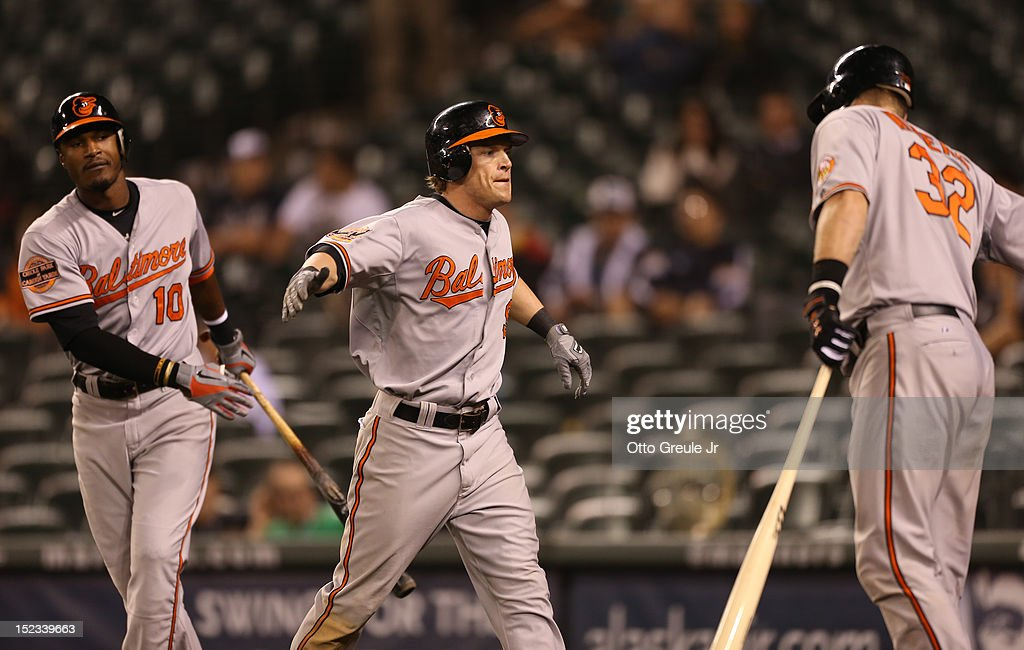 Nate McLouth #9 of the Baltimore Orioles is congratulated by Matt Wieters #32 and Adam Jones #10 after scoring in the eighteenth inning against the Seattle Mariners at Safeco Field on September 18, 2012 in Seattle, Washington.