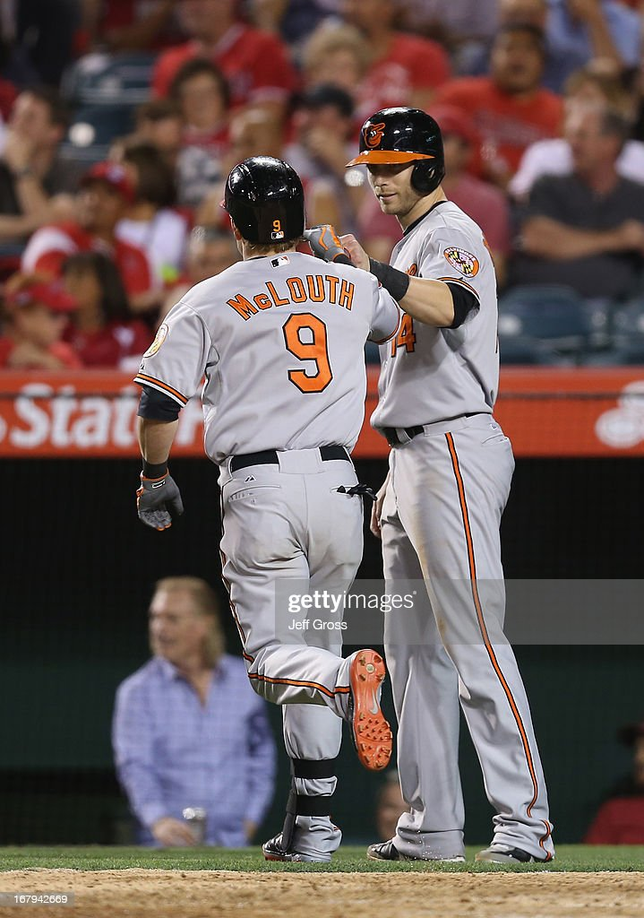 <a gi-track='captionPersonalityLinkClicked' href=/galleries/search?phrase=Nate+McLouth&family=editorial&specificpeople=536572 ng-click='$event.stopPropagation()'>Nate McLouth</a> #9 of the Baltimore Orioles is congratulated by <a gi-track='captionPersonalityLinkClicked' href=/galleries/search?phrase=Nolan+Reimold&family=editorial&specificpeople=757348 ng-click='$event.stopPropagation()'>Nolan Reimold</a> #14 after hitting a two-run home run against the Los Angeles Angels of Anaheim in the ninth inning at Angel Stadium of Anaheim on May 2, 2013 in Anaheim, California. The Orioles defeated the Angels 5-1.